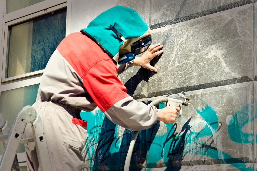 Porter Removing Graffiti From a Commercial Building