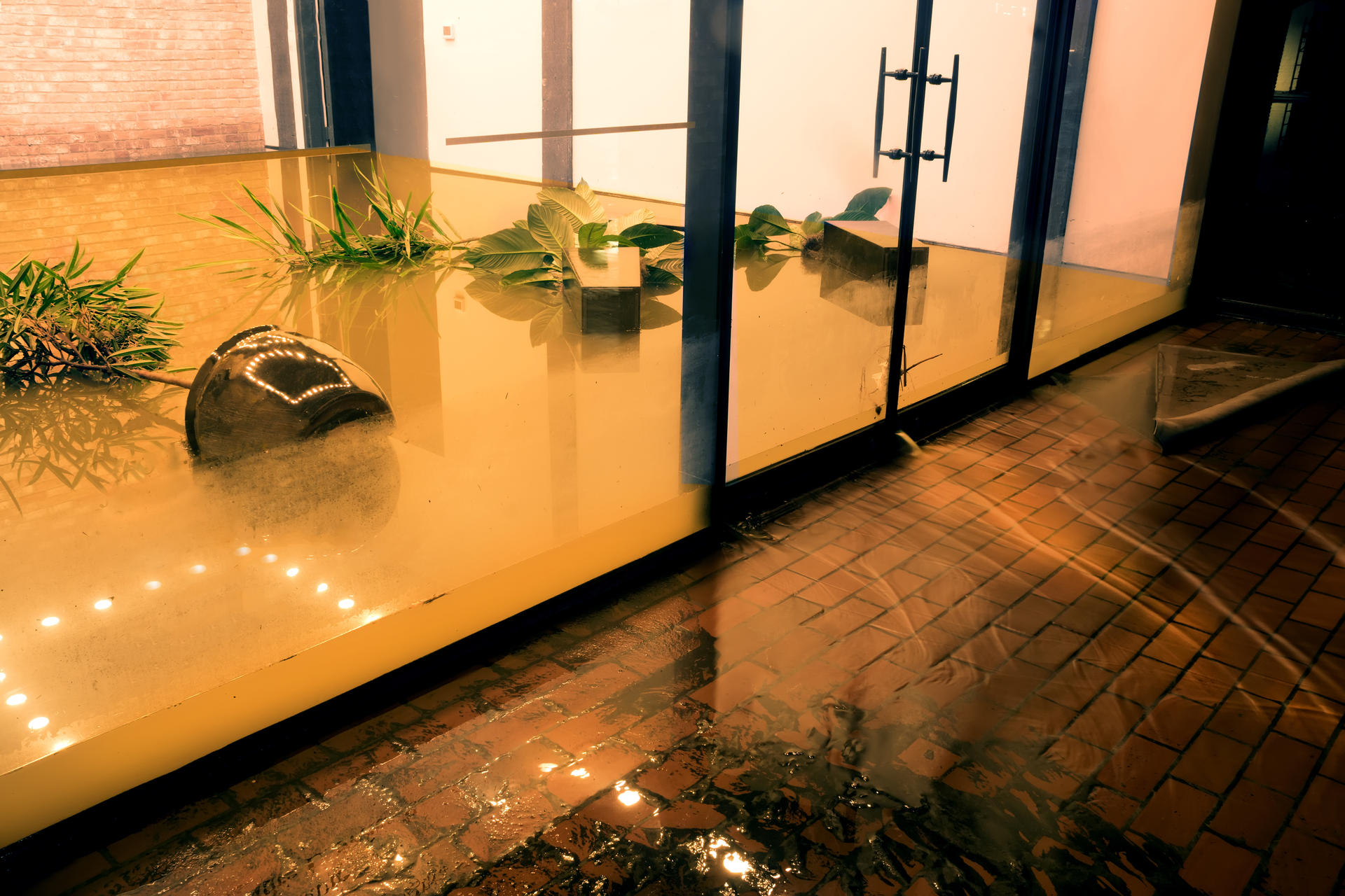 Water flowing through doors from a flooded office.