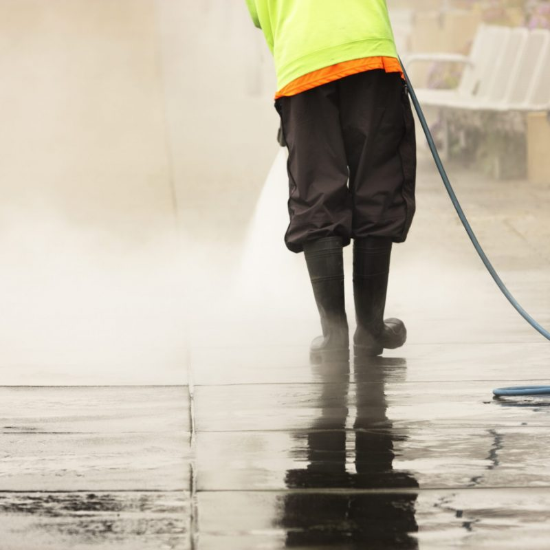 City worker steam cleans sidewalk to remove debris from the tourist trade traffic.  San Francisco, California, 2012.
