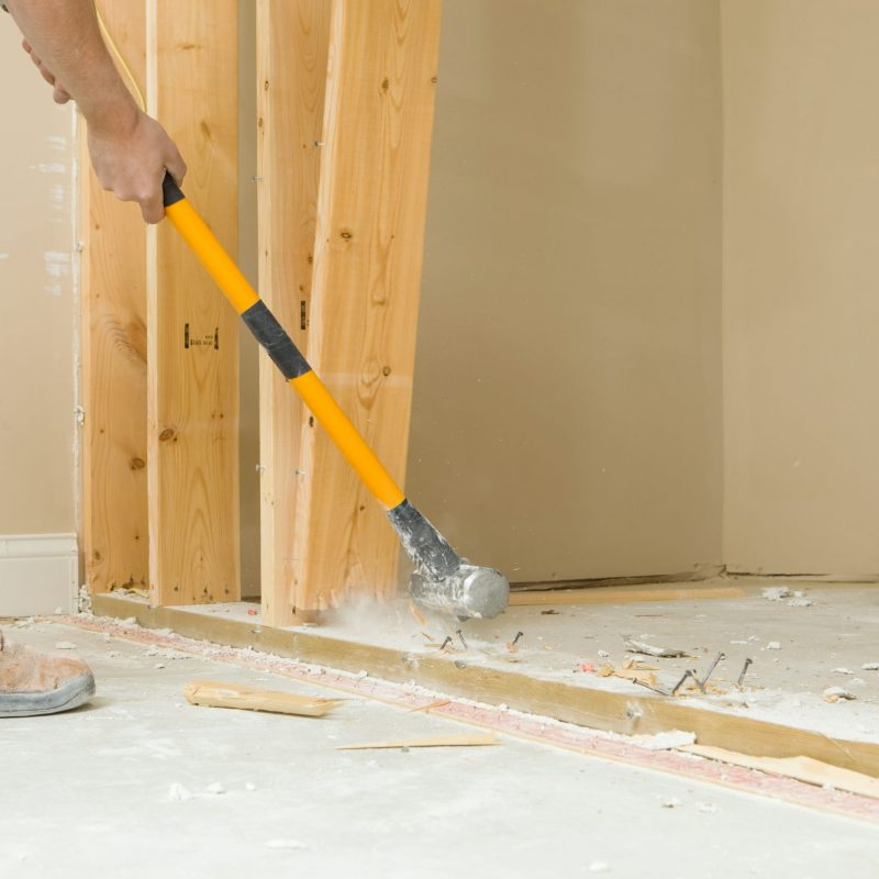 Construction Worker Using a Sledgehammer to Remove Wall Stud